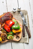 Roasted vegetables and steak with herbs on wooden board — Stock Photo