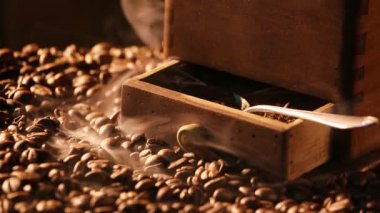 Coffee grinder standing on freshly roasted coffee beans — Stock Video