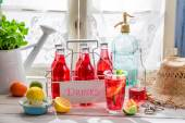 Tasty red orangeade in bottle with mint leaf — Stock fotografie