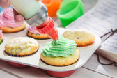 Decorating sweet cupcakes with cream and decoration — Stock Photo