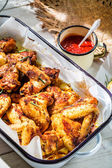 Crispy chicken wings in rustic kitchen — Stock Photo