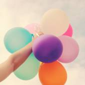 Hand holding multicolored balloons — Stock Photo