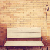 Wooden chair on brick wall — Stock Photo
