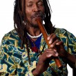 Rastafarian playing the flute — Stock Photo #65281511
