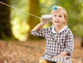 Girl listening on a tin can communicator. — Stock Photo