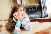 Kid  girl near fireplace — Stock Photo