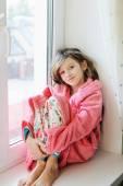 Beautiful little girl in bathrobe near window — Stock Photo