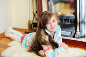 Kid  girl near fireplace — Stockfoto