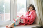 Beautiful little girl in bathrobe near window — Foto de Stock