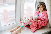 Beautiful little girl in bathrobe with cup of tea — Photo