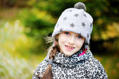 Kid girl has fun in garden with first snow — Stock Photo
