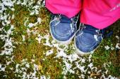 Blue kids boots on the grass with snow — Stock Photo