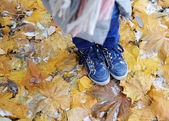 Blue kids boots on the leaves with snow — Stock Photo