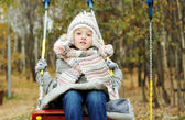Kid girl  on a swing at beautiful winter day — Stock Photo