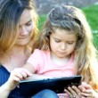 Happy mother and daughter playing on the tablet computer outdoors — Stock Video #68849795