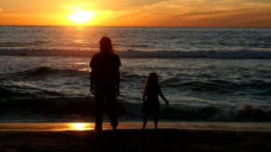 Mother and daughter enjoy a beautiful sunset by the ocean. Slow motion — Stock Video