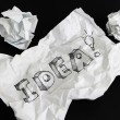 Crumpled paper sheet with word Idea isolated on black — Stock Photo #60034977