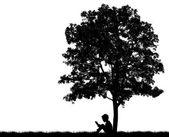 Silhouetten von kindern lesen buch unter baum — Stockfoto