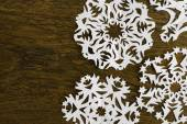 White paper christmas snowflake on a wood background — Stock Photo
