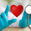 Doctor with stethoscope and red heart  in hand — Stock Photo #61799179