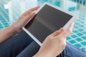 Woman working with tablet sitting at swimming pool — Stock Photo