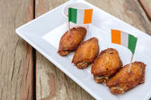 Chicken wings on wooden table — Stock Photo