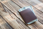 Blank passport with US dollars on wood table — Stock Photo