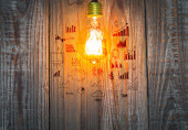 Glowing bulb with drawing graph on the wood background — Stock Photo