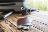 Blank passport and camera with US dollars on wood table — Stock Photo
