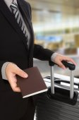 Business traveling pulling suitcase and holding passport — Stock Photo