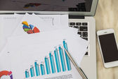 Financial charts on the table with laptop — Stock Photo