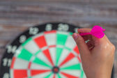 Hand holdin red arrow and throwing to dart board — Stock Photo