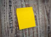 Yellow sticky note on wooden board — Stock Photo