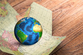 Earth in map  on wood background — Stock Photo