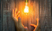 Hand with Glowing bulb on the wood background — Stock Photo