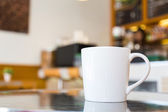 Coffee cup on table in cafe — Stock Photo