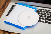 Blank compact disc with cover on laptop keyboard — Stock Photo