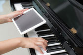 Woman hand using tablet and  playing piano music — Stock Photo