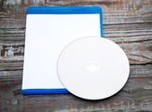 Blank compact disc with cover on wood background — Stock Photo
