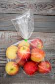Apple fruit in plastic bag on wood table — Stock Photo