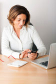 Businesswoman in office using smartphone — Stock Photo