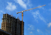 High-rise building under construction and crane — Stock Photo