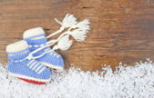 Wooden background with baby's bootees and winter snow on the bor — Stock Photo