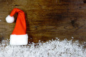 Wooden background with santa cap, snow on the border and copyspa — Stock Photo