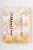 Chiacchiere, italian Carnival pastry on white tablecloth — Stock Photo