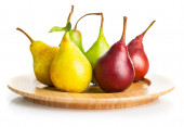Fresh pears on the wooden plate — Stock Photo