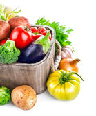 Fresh vegetables in wooden bucket with greens — Stock Photo