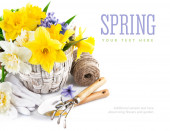 Spring flowers in basket with garden tools — Stock Photo