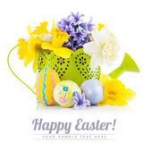 Easter eggs with spring flowers in watering can — Stock Photo