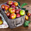 Fresh plums in wooden basket with green leaves — Stock Photo #78627820